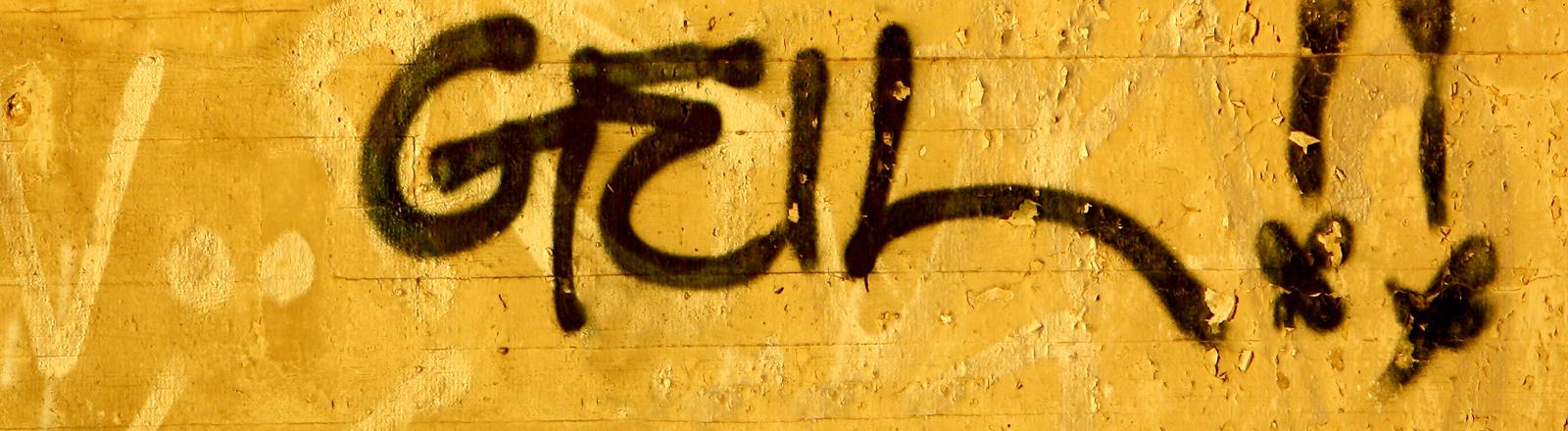 """Auf einer gelben Wand steht """"geil""""."""
