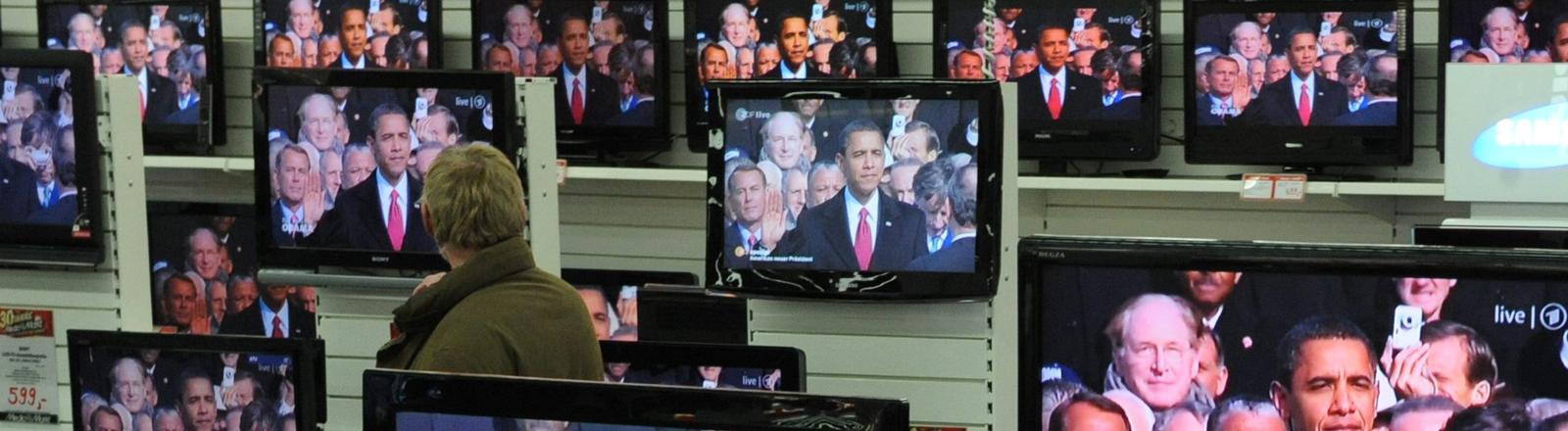 Kunden eines Technikhauses verfolgen am Dienstag (20.01.2009) in Hannover die offizielle Vereidigungszeremonie des neuen US-Präsidenten Barack Obama.
