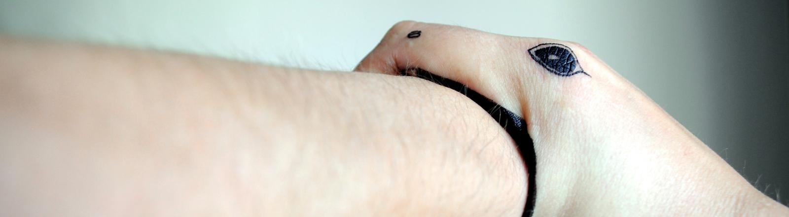 Es sieht so aus, als würde eine Schlange in einen menschlichen Arm beißen. Tatsächlich ist es eine Hand.