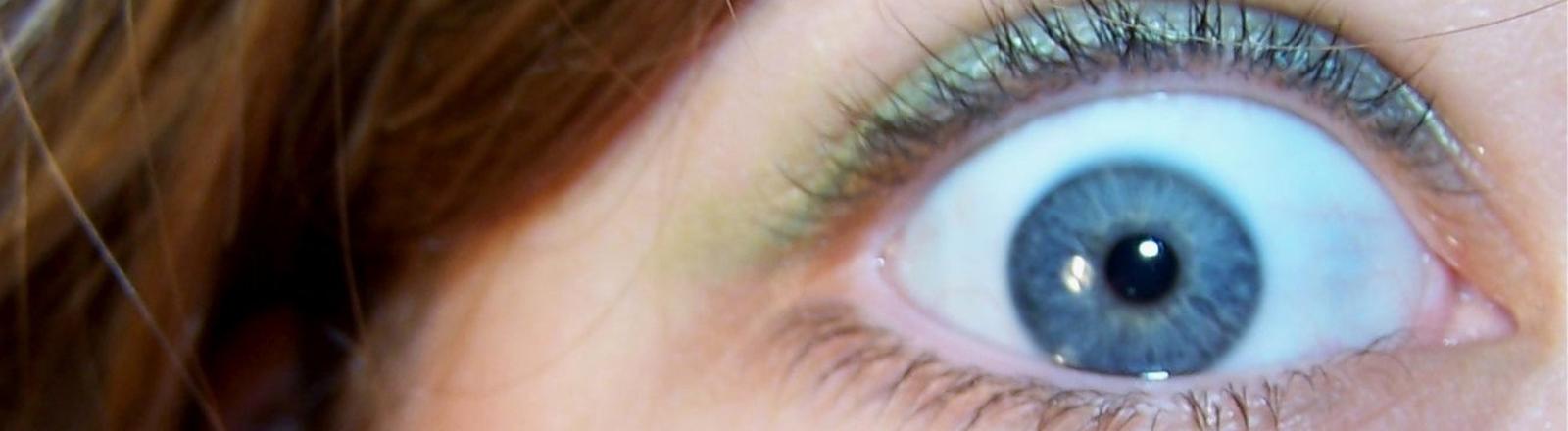 Eine Frau reißt die Augen auf vor Angst oder Schreck.