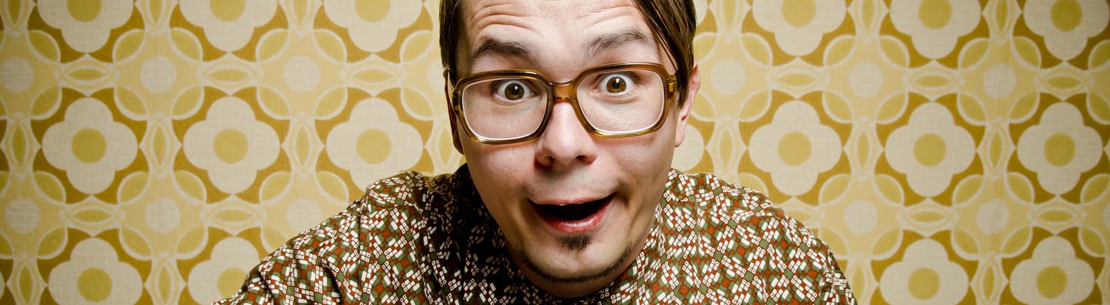Ein lustiger Mann mit einer Brille sitzt vor einem Computer und tippt auf einer Tastatur.