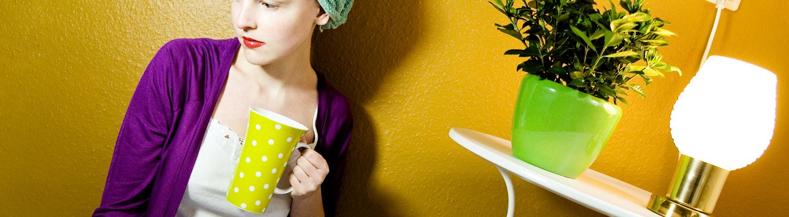 Eine Frau mit einer Tasse Tee in der Hand.