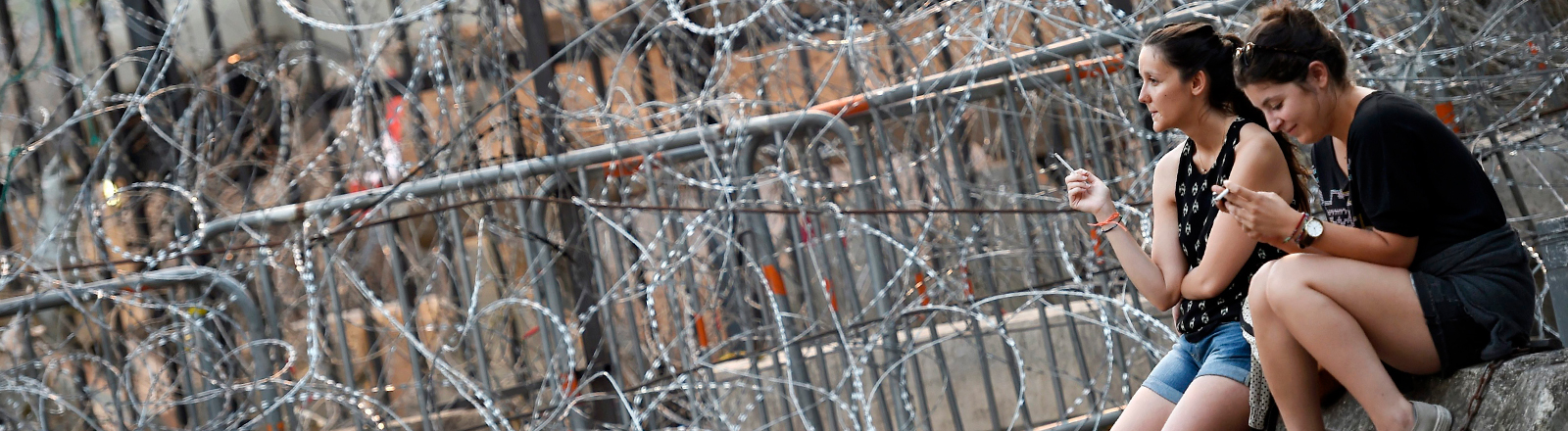 ebanese people smoke cigarettes in front barbed wire blocking the entrance to the Grand Serail, the office of the Lebanese Prime Minister, Beirut, Lebanon, 02 September 2015. Lebanese people's frustration with the Government's internecine conflicts which have paralyzed the political process has manifested in days of protests sparked by mounting garbage piled on streets, but becoming a criticism of the political class in general, seen as corrupt, cronyist and self serving