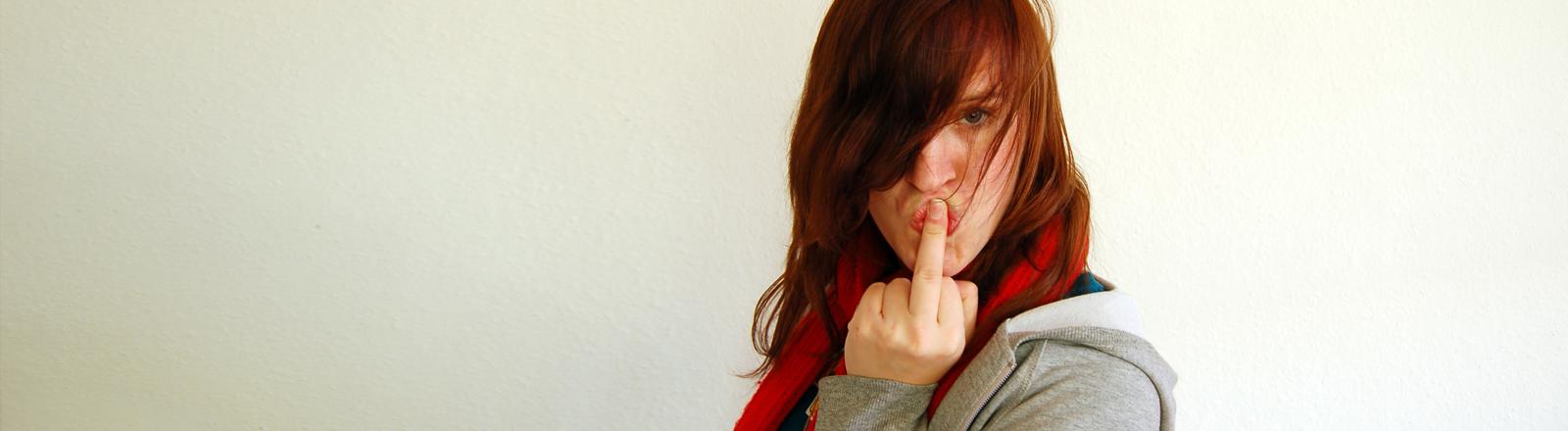 Eine Frau nimmt Abschied und zeigt dabei den Mittelfinger. Vielleicht denkt sie sich auch: Fickt euch alle.