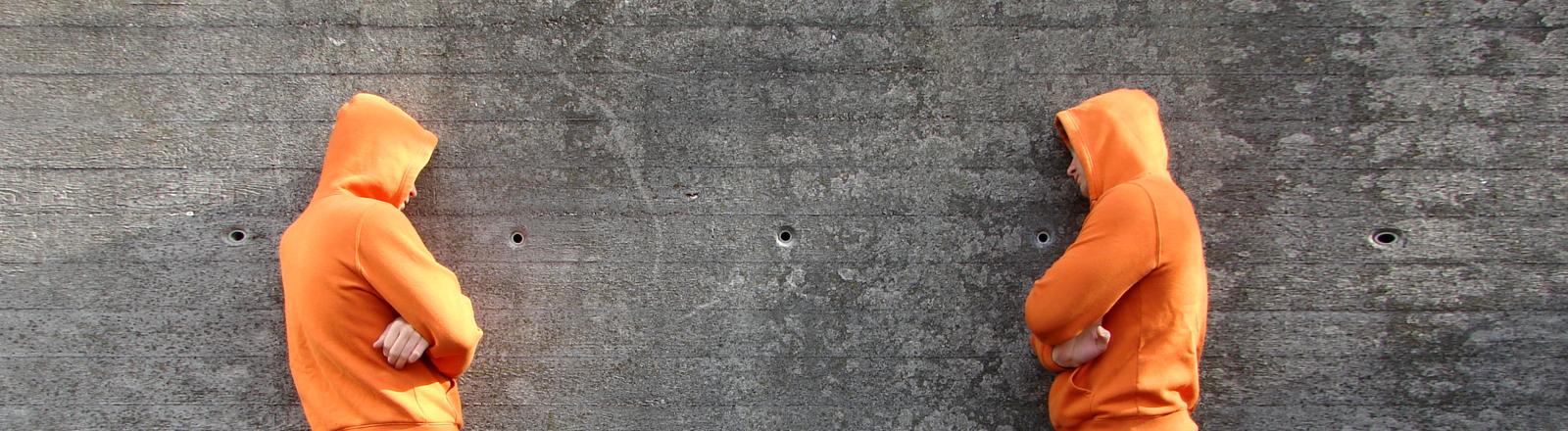 Zwei Männer stehen an einer Wand und haben Streit