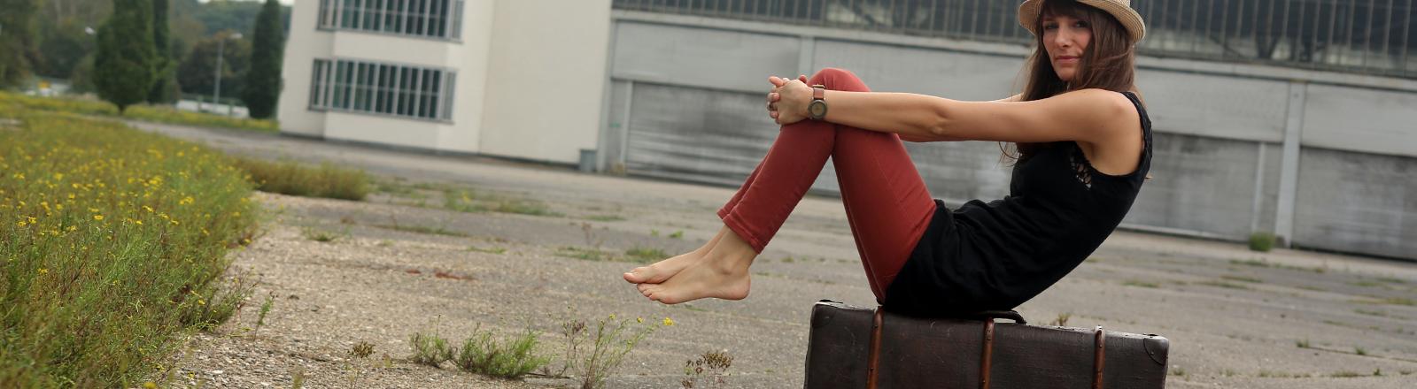 Eine Frau sitzt auf ihrem Koffer am Flughafen.