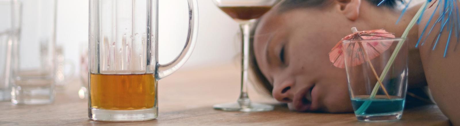 Eine Frau liegt nach einer Party betrunken auf dem Tisch und schläft.