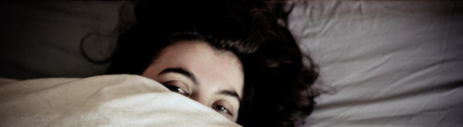 Eine Frau liegt im Bett und versucht zu schlafen.