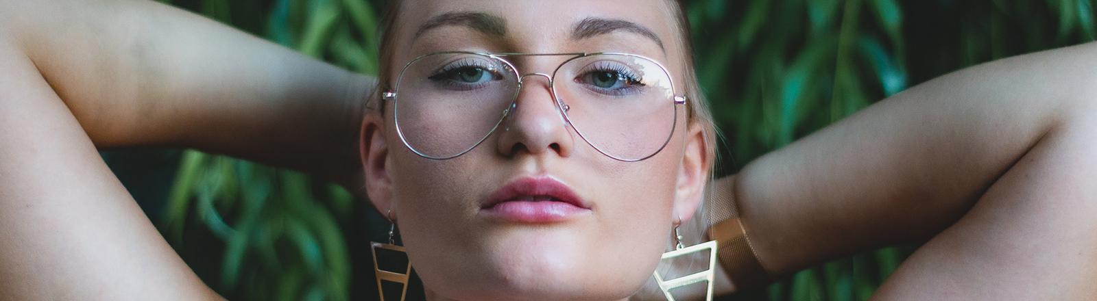 Eine Frau mit einer Brille hat die Arme hinterm Kopf verschränkt und schaut direkt in die Kamera.