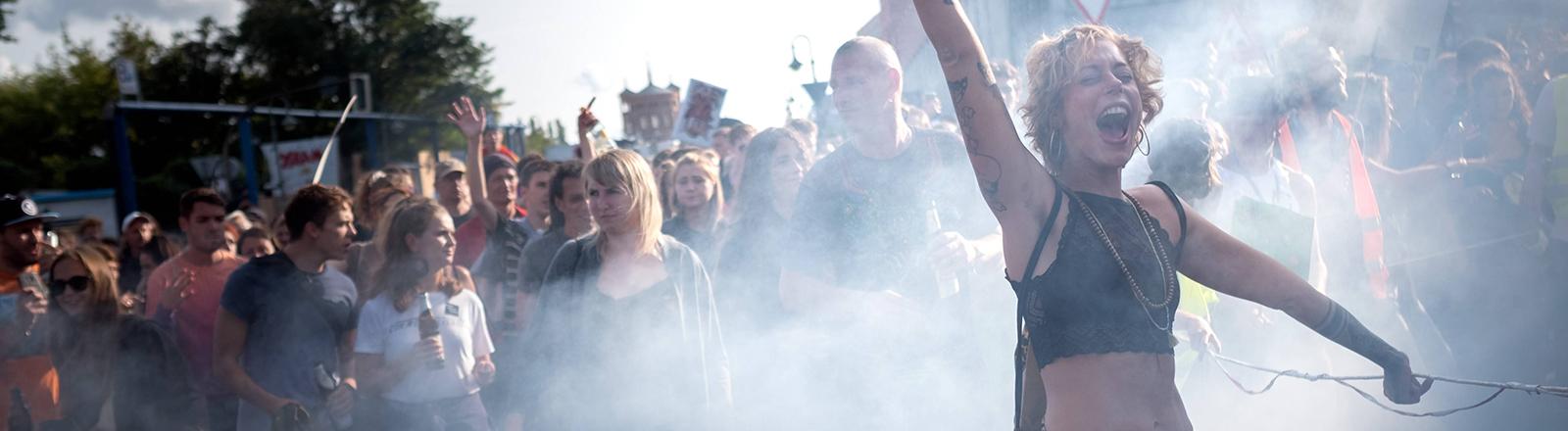 Eine Person tanzt in einer Menschenmenge und ist in Nebel gehüllt.