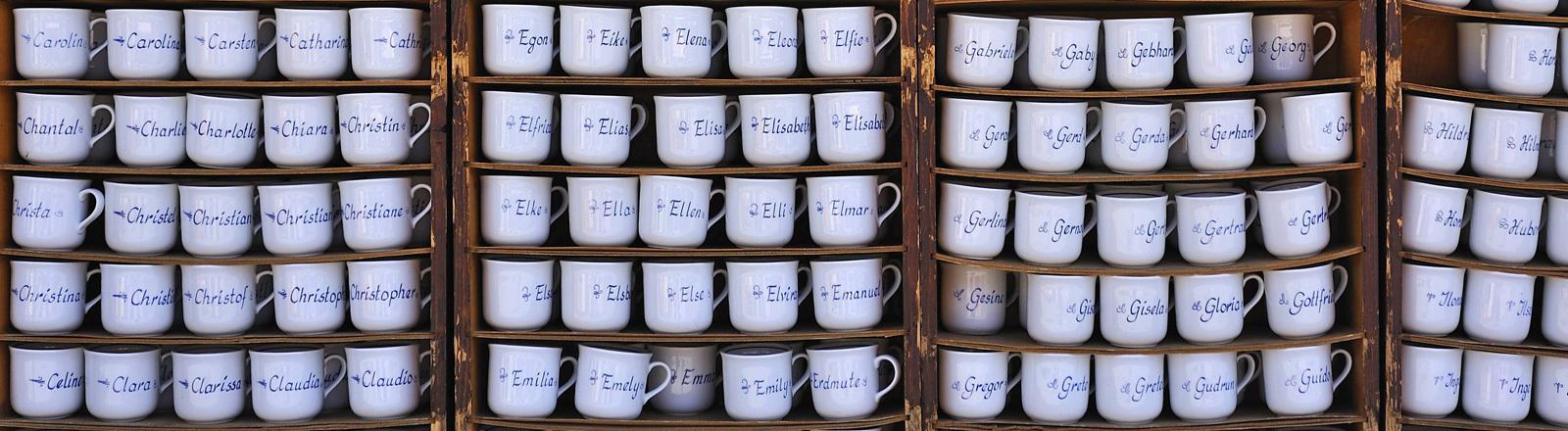 Ein Regal voller Tassen, auf denen diversen Vornamen stehen.