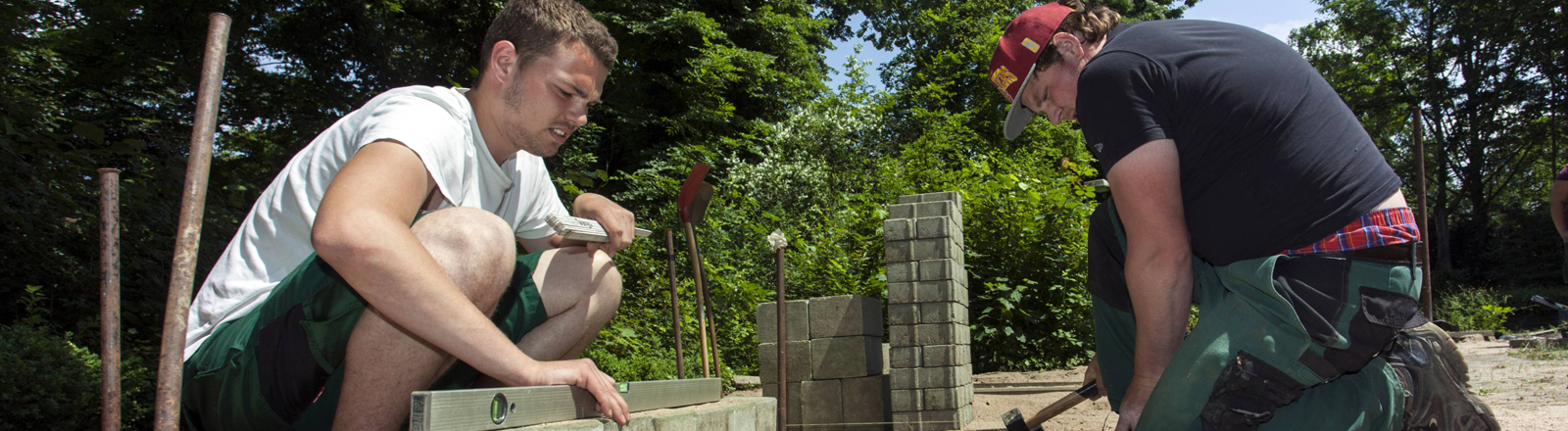 Zwei junge Azubis arbeiten auf dem Bau.