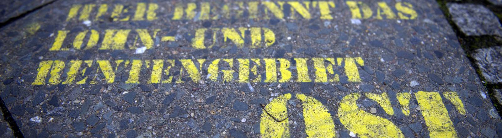 """Auf eine Straße ist """"Achtung, hier beginnt das Lohn- und Rentengebiet Ost"""" in gelber Farbe gesprüht"""