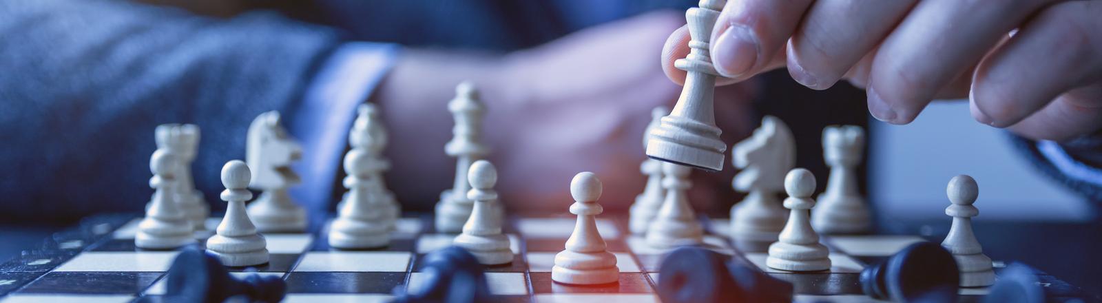 Nahaufnahme einer Hand beim Schachspiel. Die weißen Figuren stehen noch, alle schwarzen sind umgefallen.