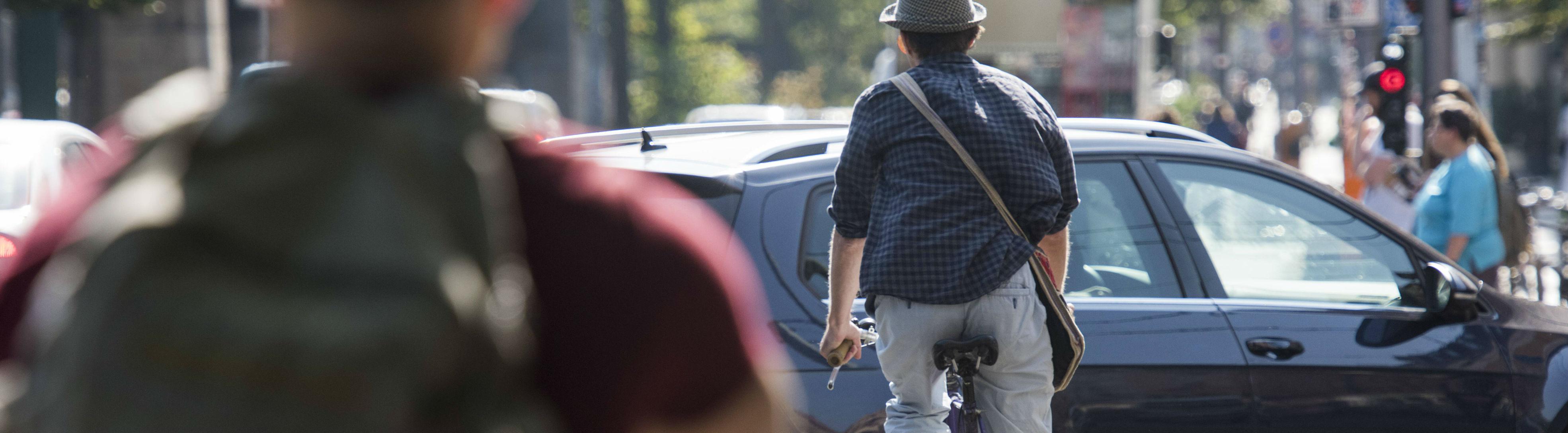 Ein Fahrradfahrer in Berlin wird von einem Auto geschnitten.