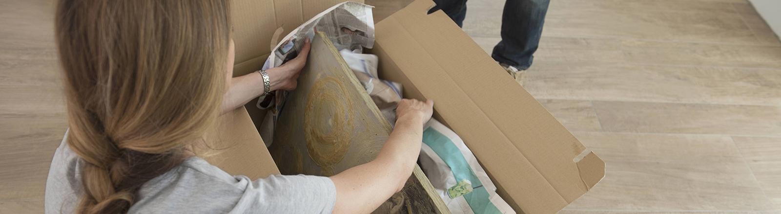Eine Person kniet auf dem Boden und packt Gegenstände in eine Kiste.