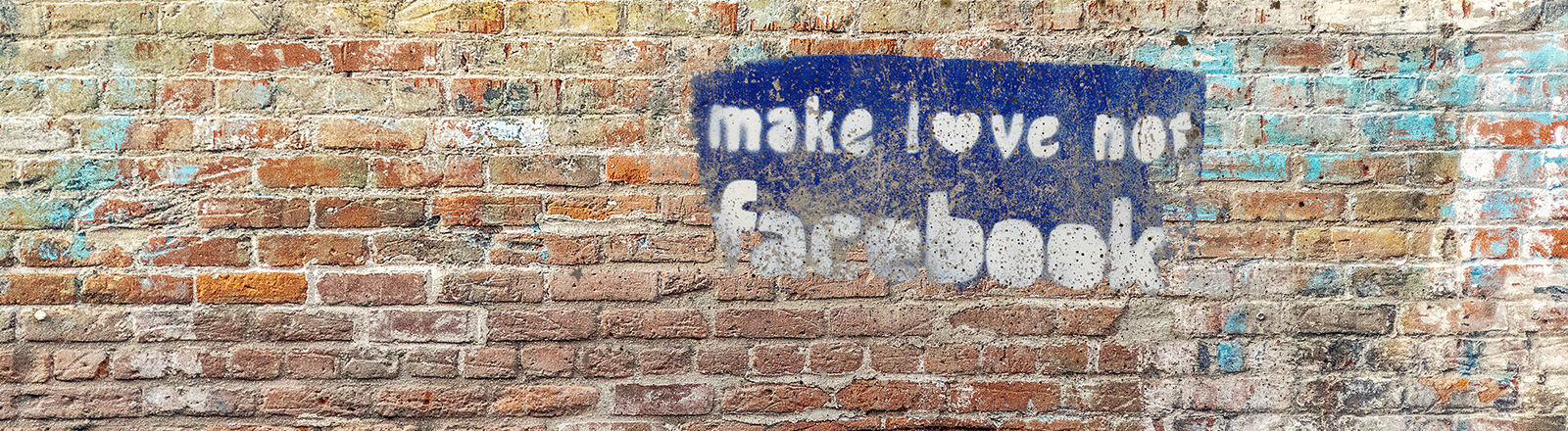 Eine Backsteinwand mit einem Grafitto: Make love not facebook.