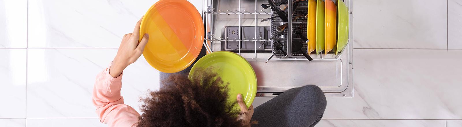 Frau räumt Spülmaschine aus.