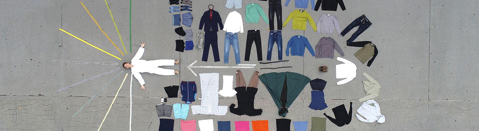 Eine Person liegt auf dem Boden, darum herum sind Kleidungsstücke ausgelegt.