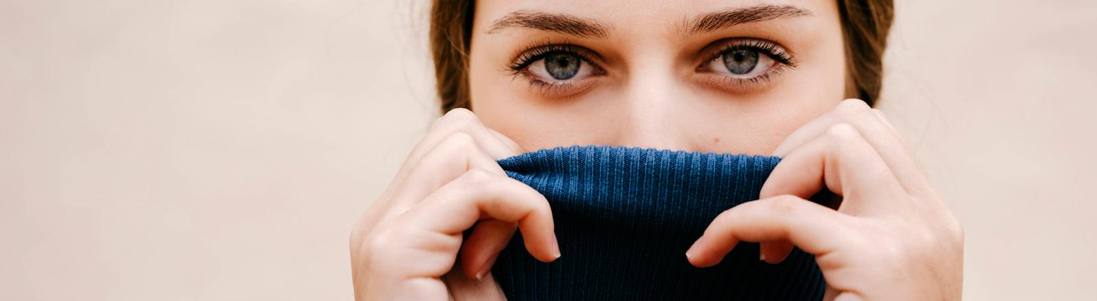 Eine Frau kuschelt sich in ihren Pullover.