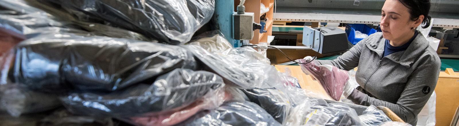 Eine Mitarbeiterin kontrolliert im Hermes Rücksendezentrum die Ware aus Paketen mit Retouren.