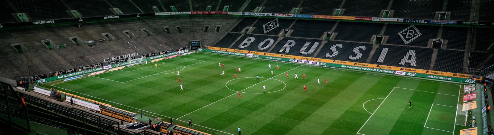 Die Mönchengladbacher und die Kölner Spieler kämpfen um den Ball. Das Spiel findet wegen des Coronavirus ohne Zuschauer als Geisterspiel statt.