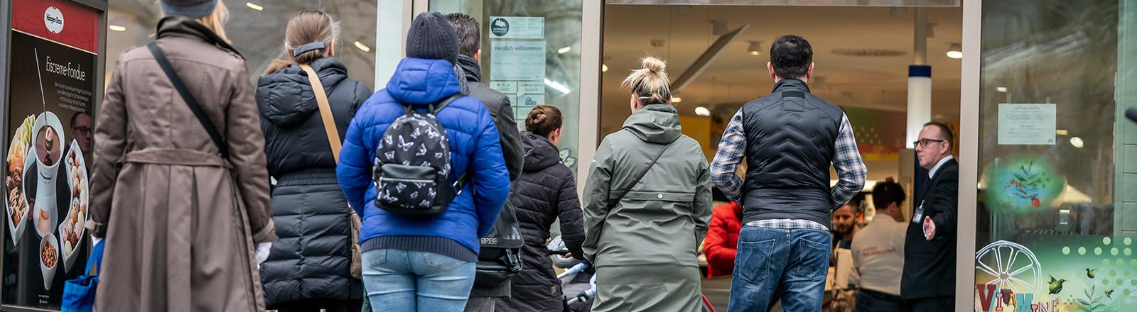 Menschen stehen in der Schlange vor einem Drogeriemarkt (20.03.2020)