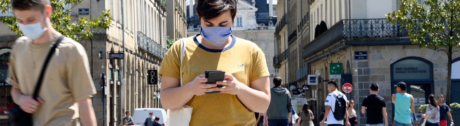 Ein Mann in Frankreich schaut auf sein Handy.