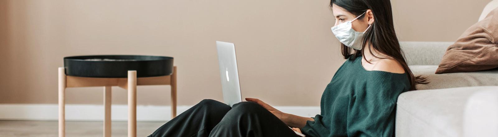 Eine junge Frau mit Mundschutz sitzt am Computer.