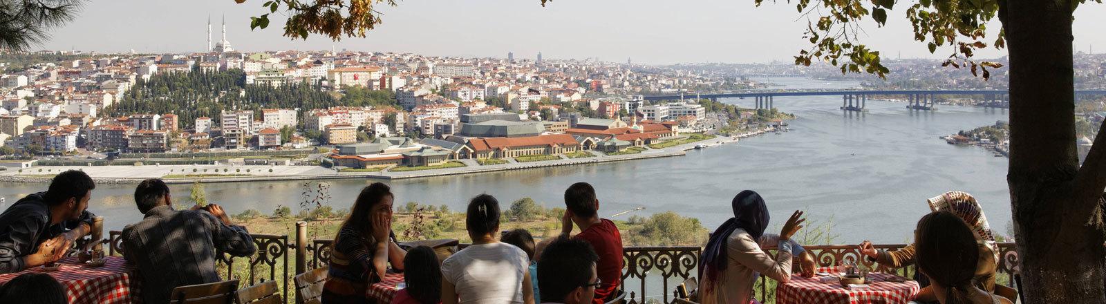 Menschen in einem Istanbuler Café in einem Park auf einer Anhöhe mit Blick auf den Bosporus.