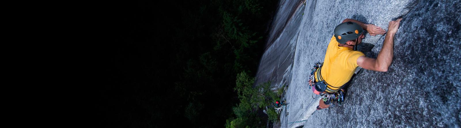 Ein Mann klettert eine steile Felswand hoch.