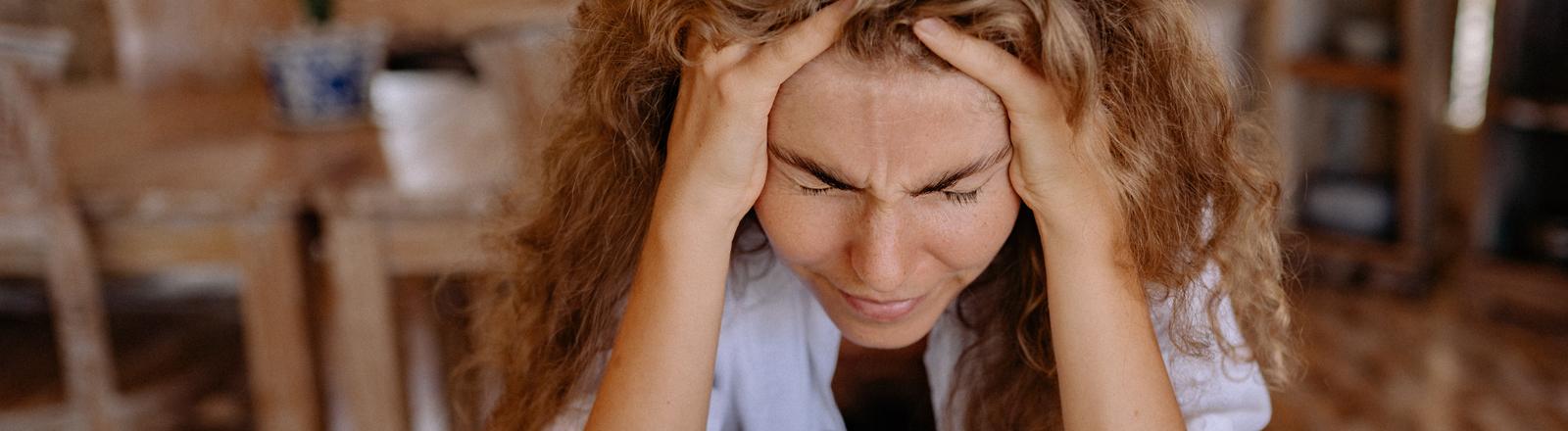 Eine Frau stützt gestresst den Kopf auf die Hände.