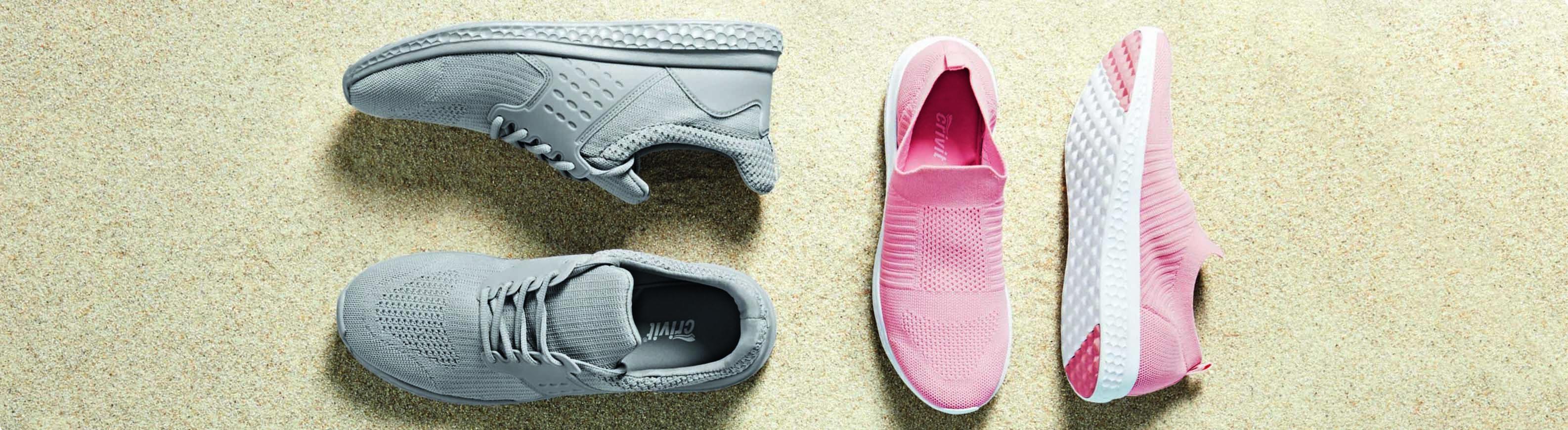 Ein Paar graue und ein Paar rosafarbene Sneaker liegen am Strand.