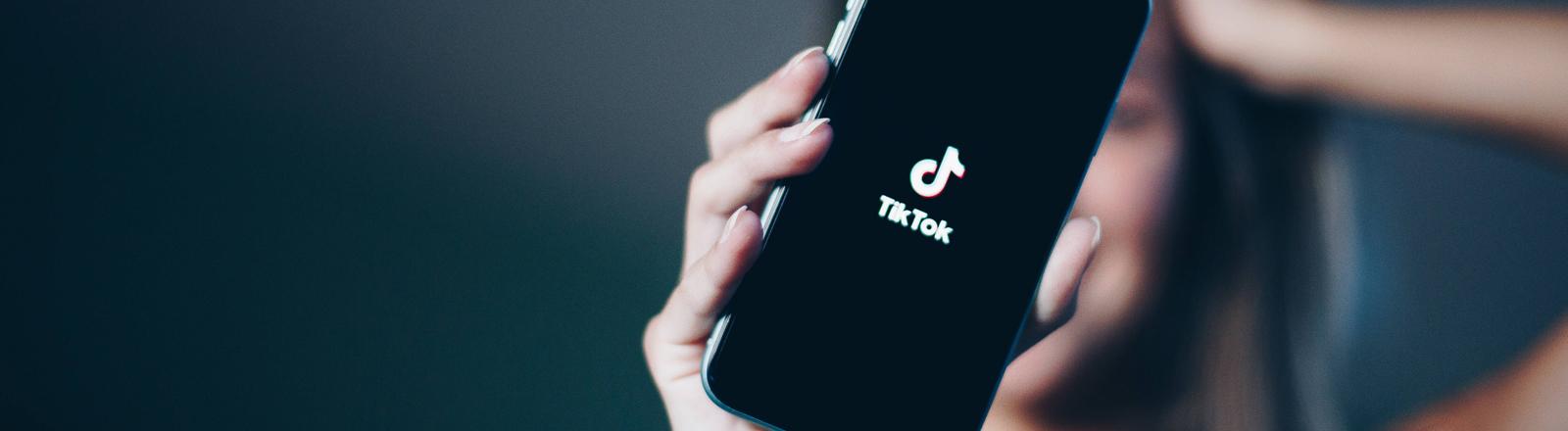 Frau hält ein Handy mit der TikTok-App.