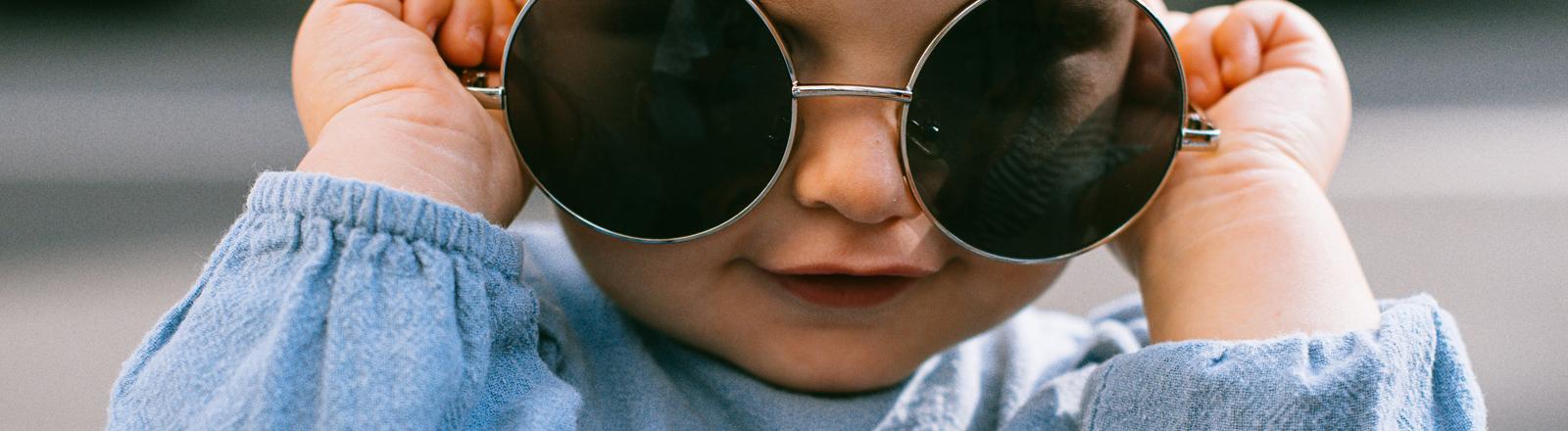 Ein Baby trägt eine Sonnenbrille.