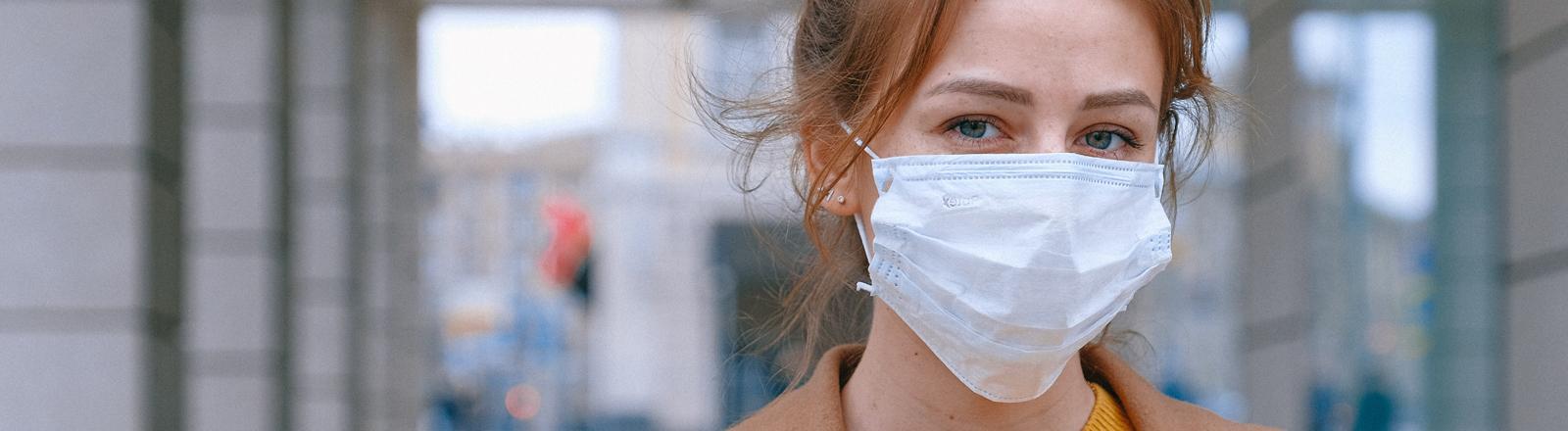Eine Frau trägt einen Mund-Nasen-Schutz.