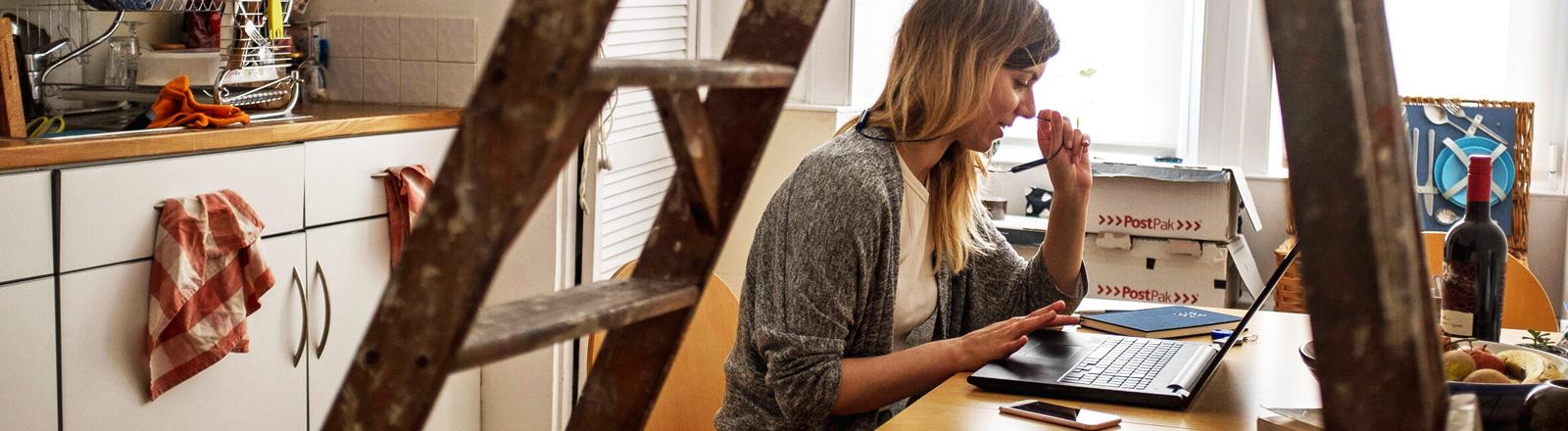 Eine Frau sitzt am Küchentisch und arbeitet im Homeoffice.