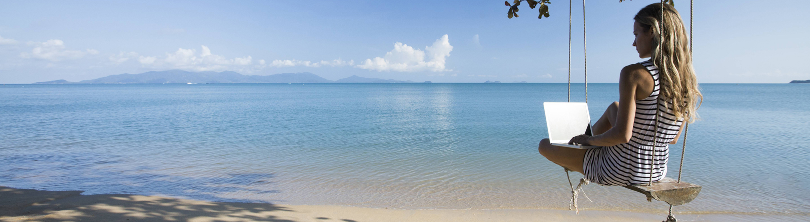 Eine Frau sitzt am Strand mit ihrem Laptop.