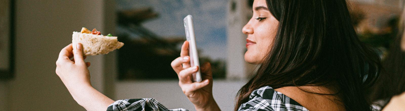 Eine Frau macht ein Handyfoto von ihrem Brötchen.