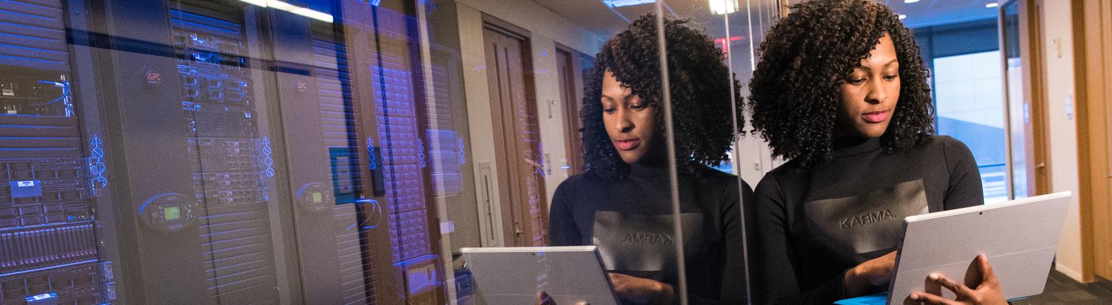 Eine Frau schaut in einem Rechenzentrum auf ihren Laptop.