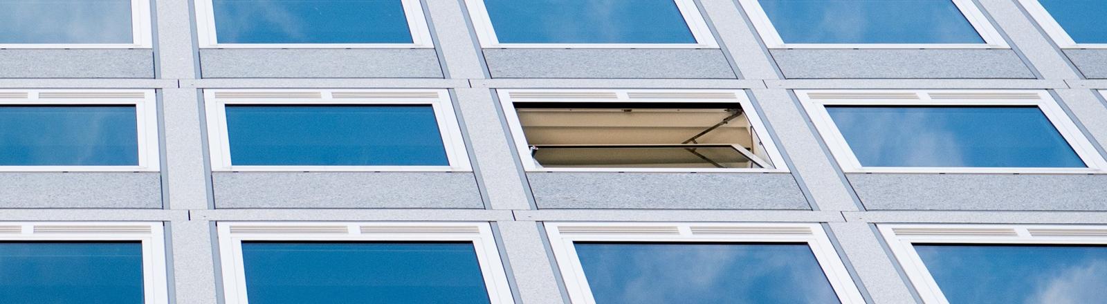 Die Fassade eines Bürogebäudes, ein Fenster steht auf kipp.