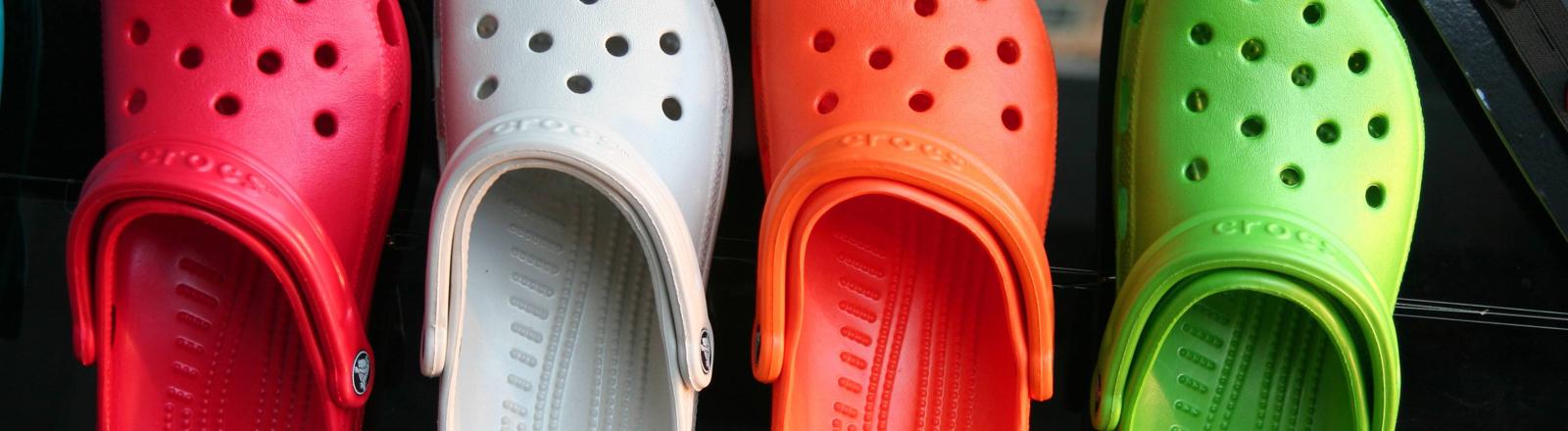 Vier bunte Crocs nebeneinander.