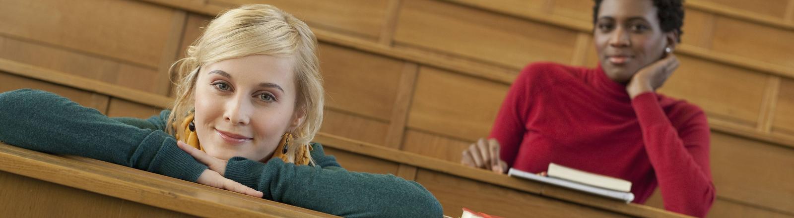 Zwei Studentinnen sitzen im Hörsaal.