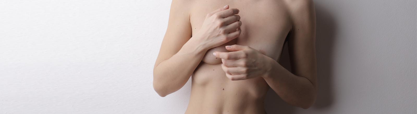 Eine Frau verbirgt mit den Händen ihre Brüste.