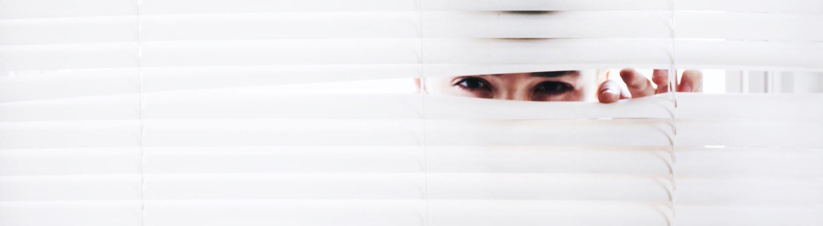 Eine Frau schaut durch eine Jalousie.