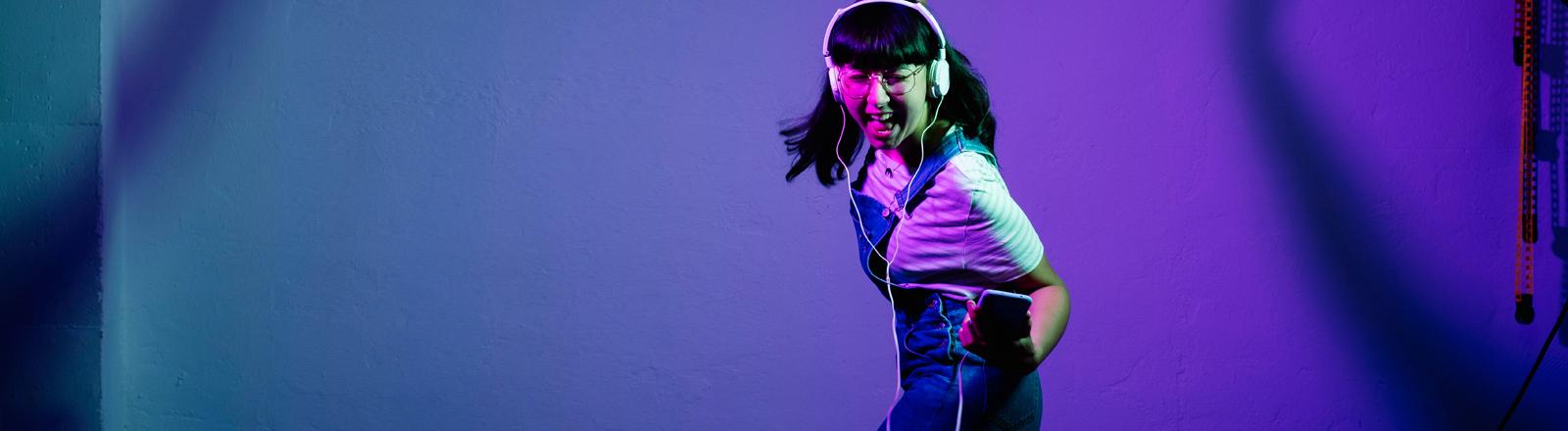 Eine Frau tanzt glücklich und hält ihr Handy dabei in der Hand.