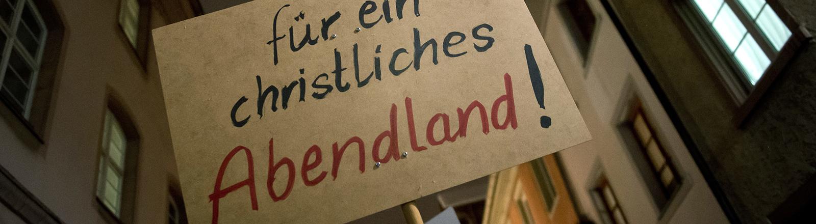 """Bei einer Demonstration in Villingen-Schwenningen halten Pegida-Anhänger ein Schild in die Höhe, darauf steht """"für ein christliches Abendland""""; das Foto zeigt das Plakat und im Hintergrund Häuser (26.01.2015); Foto:dpa"""