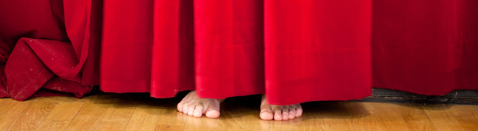 Roter Theatervorhang, unter dem ein paar nackte Füße hervorschauen.