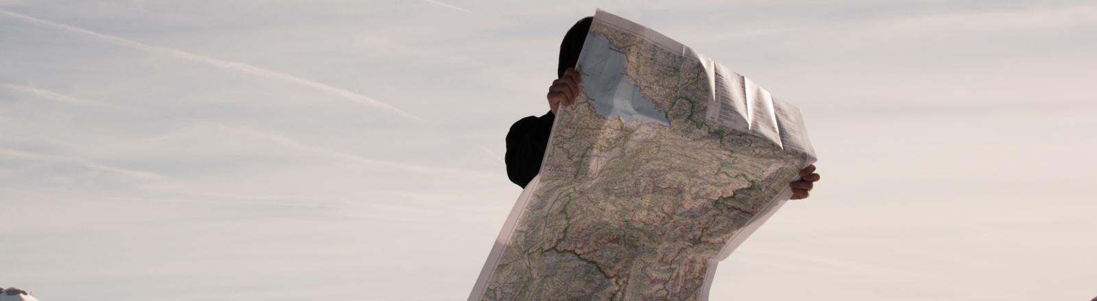 Ein Mensch steht mit einer Karte aus Papier auf einem Berg und scheint den Weg zu suchen.