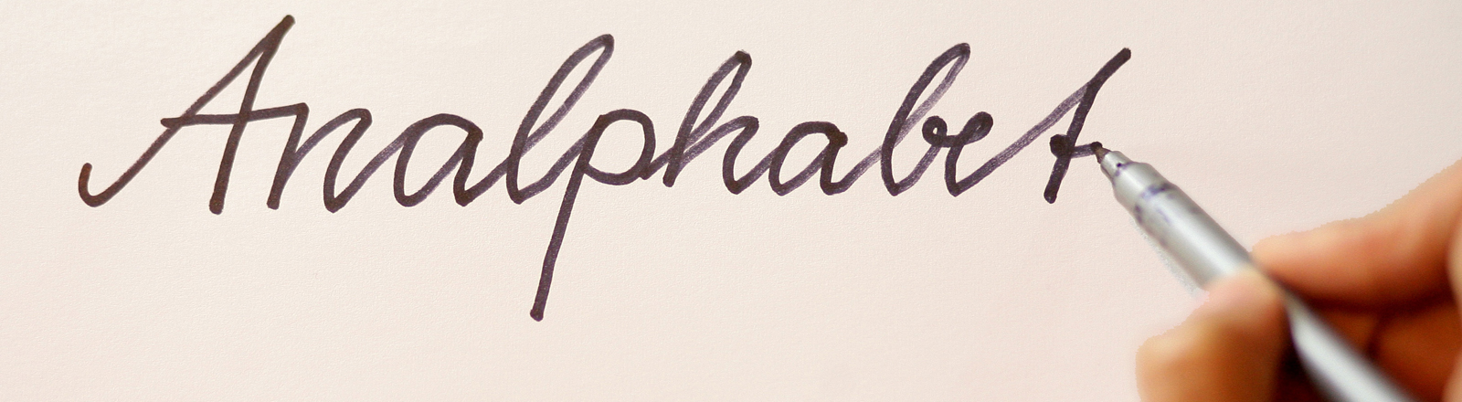 """Eine Hand, die einen Stift hält, mit dem sie das Wort """"Analphabet"""" schreibt."""